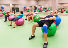 Young people doing exercises in the gym Stock Photo