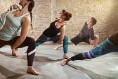 Young people doing flexibility exercise. Class of body balance Royalty Free Stock Images