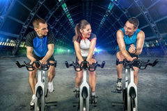 Young people doing spinning. On cycle bike Royalty Free Stock Image