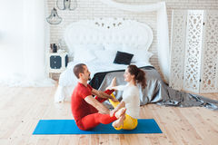 Young people doing sports exercises. Young people doing sport exercises in the morning in the bedroom Royalty Free Stock Photography