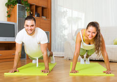 Young people doing yoga indoor. Young smiling people doing yoga on mats in room Stock Photo