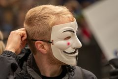 Young people dressed all in black goes out on the street to demonstrate with anonymous masks stock image