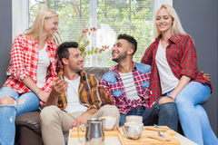 Young people drink coffee shop, friends sitting table smiling Royalty Free Stock Photography
