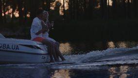 Young people drinking champagne on floating motor boat. Boating on river stock video footage