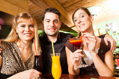 Young people drinking cocktails in bar. Young happy people drinking cocktails in bar or restaurant; presumably it is a little party Royalty Free Stock Photo