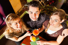 Young people drinking cocktails in bar or restaurant. Young happy people drinking cocktails in bar or restaurant; presumably it is a little party Stock Photo