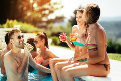 Young people drinking cocktails at swimming pool royalty free stock image