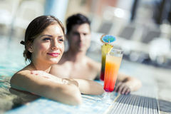 Young people drinking cocktails by the swimming pool and relaxin Royalty Free Stock Photos
