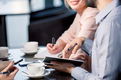 Young people drinking coffee and writing in notebooks at business meeting, business lunch concept. Close-up partial view of young people drinking coffee and Royalty Free Stock Image