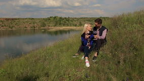 Young people drinking wine at a picnic near lake. Couple in love drinking wine sitting on the grass near a large lake. Young people drinking wine at a picnic stock footage