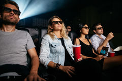 Young people with drinks watching 3d film Royalty Free Stock Photography