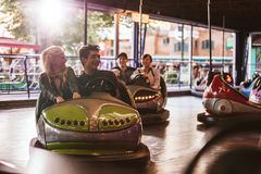 Young people driving bumper car at amusement park Royalty Free Stock Photo