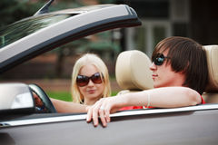 Young fashion people driving convertible car Stock Photos
