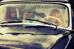 Young people driving retro car in the rain Stock Photography