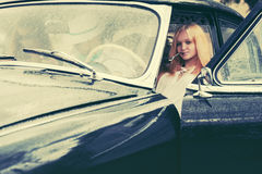 Young people driving retro car in the rain Stock Images
