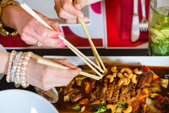 Young people eating food in Thai restaurant. Young people eating in a Thai restaurant, they eating with chopsticks, close-up on hands and food stock images