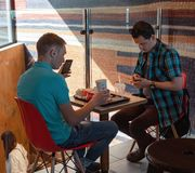 Young people eating in a Mcdonald`s. KYIV, UKRAINE - May 05, 2017: Young people have a rest and eating in a Mcdonald`s in Kyiv, Ukraine. Mcdonald`s is a very royalty free stock photos