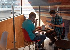 Young people eating in a Mcdonald`s. KYIV, UKRAINE - May 05, 2017: Young people have a rest and eating in a Mcdonald`s in Kyiv, Ukraine. Mcdonald`s is a very stock photography