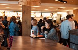 Young people eating in a Mcdonald`s. KYIV, UKRAINE - May 05, 2017: Young people have a rest and eating in a Mcdonald`s in Kyiv, Ukraine. Mcdonald`s is a very royalty free stock photography