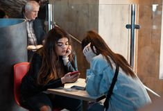 Young people eating in a Mcdonald`s. KYIV, UKRAINE - May 05, 2017: Young people have a rest and eating in a Mcdonald`s in Kyiv, Ukraine. Mcdonald`s is a very stock images