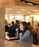 Young people eating in a Mcdonald`s. KYIV, UKRAINE - May 05, 2017: Young people have a rest and eating in a Mcdonald`s in Kyiv, Ukraine. Mcdonald`s is a very royalty free stock photo