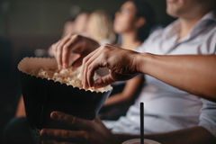 Young people eating popcorn in movie theater. Close up shot of young people eating popcorn in movie theater, focus on hands Royalty Free Stock Photos