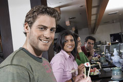 Young People Eating Sushi With Chopsticks In Restaurant Royalty Free Stock Image