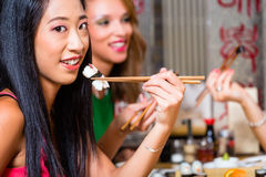 Young people eating sushi in restaurant. Young people eating sushi in Asian restaurant royalty free stock images