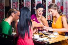 Young people eating sushi in restaurant Stock Photo