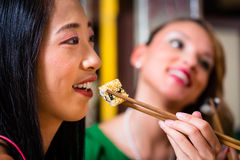 Young people eating sushi in restaurant. Young people eating sushi in Asian restaurant royalty free stock photo