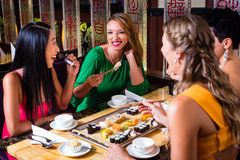 Young people eating sushi in restaurant Stock Images