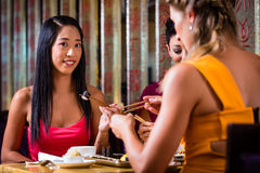 Young people eating sushi in restaurant. Young people eating sushi in Asian restaurant stock photography