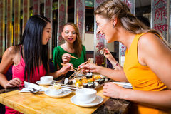 Young people eating sushi in restaurant royalty free stock photography