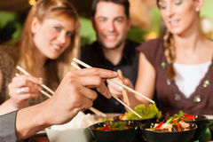 Young people eating in Thai restaurant. Young people eating in a Thai restaurant; they eating with chopsticks royalty free stock image