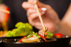 Young people eating in Thai restaurant. Young people eating in a Thai restaurant, they eating with chopsticks, close-up on hands and food royalty free stock photos