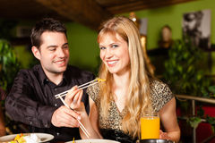 Young people eating in Thai restaurant. Young people eating in a Thai restaurant, they eating with chopsticks stock images