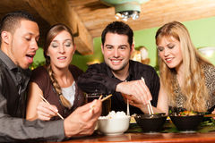 Young people eating in Thai restaurant. Young people eating in a Thai restaurant, they eating with chopsticks royalty free stock images
