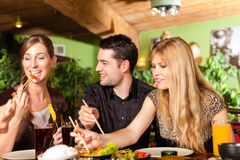 Young people eating in Thai restaurant. Young people eating in a Thai restaurant, they eating with chopsticks stock photos