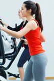 Young people with elliptic machine in the gym. Portrait of young people with elliptic machine in the gym Stock Photo