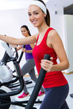 Young people with elliptic machine in the gym Stock Images