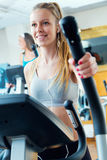 Young people with elliptic machine in the gym. Portrait of young people with elliptic machine in the gym Stock Images
