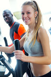Young people with elliptic machine in the gym. Portrait of young people with elliptic machine in the gym Royalty Free Stock Photography
