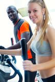 Young people with elliptic machine in the gym. Portrait of young people with elliptic machine in the gym Stock Image