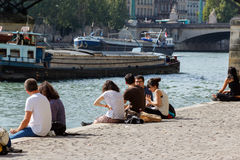 Young people on the embankment of the River Seine Royalty Free Stock Images