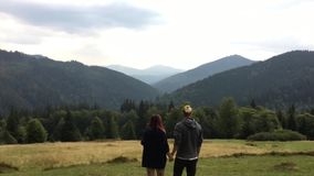 Young people embrace each other standing on the meadow. Among the mountains. Woman put her head on her partner`s shoulder stock footage