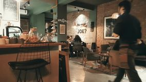 Young people enjoying the conversation in a cafe. Eskisehir, Turkey - March 08, 2017: Interior of Hey Joe Coffee Co. with young students stock footage