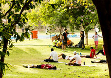 Young people enjoying an exercise class in the park. Gurgaon, India; 23rd May 2015: Young people enjoying an exercise class with yoga mats at the park in the Stock Photo