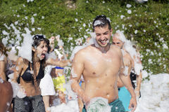 Young people enjoying  a foam party on the beach. Foam Party on the beach Royalty Free Stock Photo