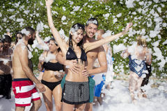 Young people enjoying  a foam party on the beach Stock Photography