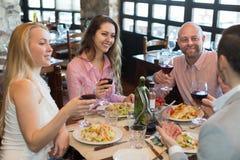 Young people enjoying food at tavern Stock Photography